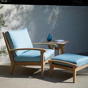 Fotel z podnóżkiem z kolekcji mebli ogrodowych marki Gloster z charakterystycznymi niebieskimi poduszkami. Fot. Gloster.