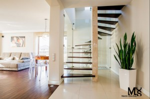 Projekt będący fuzją rozmaitych stylów, stare artdeco'wskie meble odziedziczone po babci zestawione z nowoczesnym designem- tworzą elegancką całość. Przejrzyste, jasne przestrzenie w których zadbano o każdy najmniejszy detal.  Odsłonięto schody poprzez wyburzenie ściany i oparcie ich na szklanych taflach, dzięki czemu salon zyskał na lekkości.  Motywem spajającym aranżację jest struktura betonu na ścianach: w kuchni, przedpokoju oraz małej łazience, podkreślająca eklektyczny charakter wnętrz.