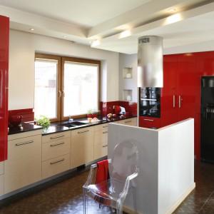 Ściany nad blatem zdobi czerwone, lakierowane szkło. Dokładnie w takim samym kolorze są szafki kuchenne. Czerwień zyskała kontrast w postaci forniru bielonego dębu, z którego wykonano fronty szafek dolnych. Projekt: Jolanta Kwilman. Fot. Bartosz Jarosz.