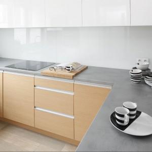 Meble kuchenne wykonane zostały z dębowego forniru połączonego z białym, lakierowanym MDF-em. Całość spina laminowany blat w szarym kolorze. Fot. Bartosz Jarosz.