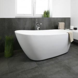 Duża, przestronna łazienka z prysznicem i wanną oszczędna jest zarówno w formie, jak i w kolorystyce. Minimalizm przede wszystkim. Fot. Bartosz Jarosz.
