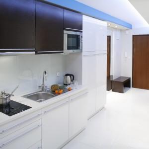 Ścianę nad blatem w białym kolorze zabezpiecza tafla z przezroczystego szkła. Biel dodaje wnętrzu przestrzeni. Dlatego w tym kolorze jest również podłoga i zabudowa kuchenna z lakierowanego MDF-u. Projekt: Agnieszka Burzyszkowska-Walkosz. Fot. Bartosz Jarosz.