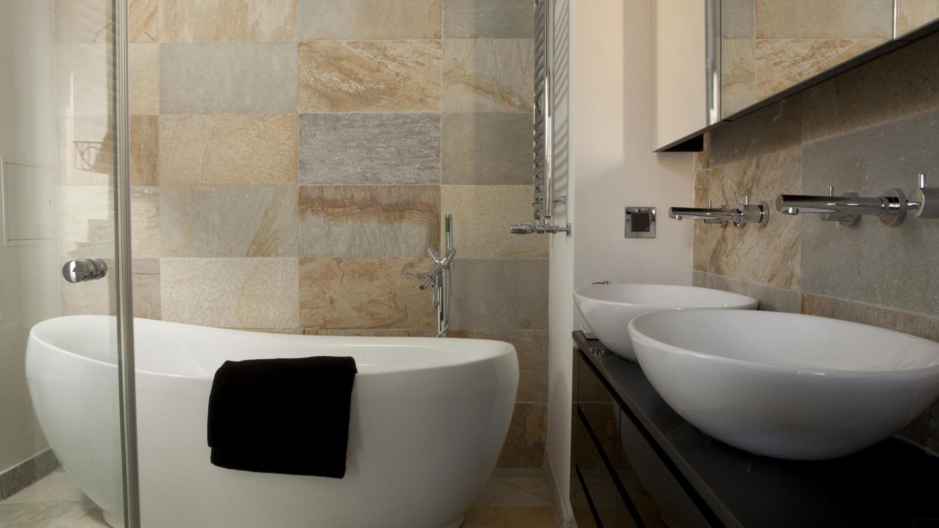 W łazience dla dwojga duża wanna to podstawowy element wyposażenia. Doskonale prezentuje się na tle imitujących kamień płytek. Projekt Magdalena Smyk. Fot. Bartosz Jarosz.