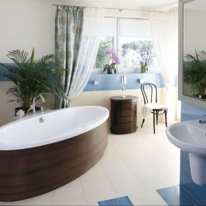 Utrzymana w nadmorskiej konwencji łazienka przyciąga kolorami morza. Wolno stojąca wanna została umiejscowiona w centralnym jej punkcie. W imitującej drewno obudowie zachęca do długich kąpieli. Projekt Marta Kruk. Fot. Bartosz Jarosz.