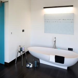 W przestronnym lofcie strefa kąpielowa została przeniesiona do sypialni. Organizuje ją wolno stojąca wanna o asymetrycznym kształcie. Projekt Justyna Smolec. Fot. Bartosz Jarosz.
