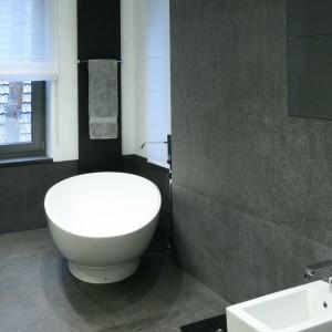 W urządzonej w minimalistycznym stylu łazience dominują szarości oraz proste, geometryczne formy. Ich symetrię przełamuje owalna wanna wolno stojąca zamontowana tuz przy oknie. Projekt Katarzyna Kiełek. Fot. Bartosz Jarosz.