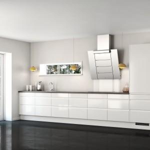 Meble z kolekcji Siena Bianco firmy Nettoline. Nowoczesne, o prostej formie. Białe lakierowane fronty w połysku, otwierane bezuchwytowo. Na zasadzie kontrastu dobrano blat, piekarnik, okap oraz podłogę. Reszta sprzętów AGD (lodówka, zmywaka, kuchenka mikrofalowa) ukryte są za białymi frontami.