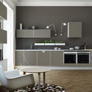 Kuchnia z kolekcji S12 firmy Svane Kitchen. Fronty lakierowane w połysku w kolorze szarym. Warto zwrócić uwagę na nieregularny układ szafek górnych oraz nietypowe, kuchenne oświetlenie. Ciemna szara ściana doskonale współgra z jaśniejszą zabudową,