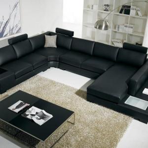 Czarną, dużą sofę w kształcie podwójnej litery L można wyznaczyć granicę salonu. Fot. agcinteriordesign.info.