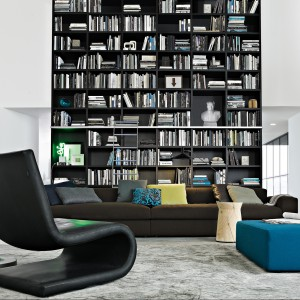 Czarna meblościanka, pnąca się aż po sufit, pomieści nawet najbardziej pokaźny zbiór książek. Fot. Mood Design.