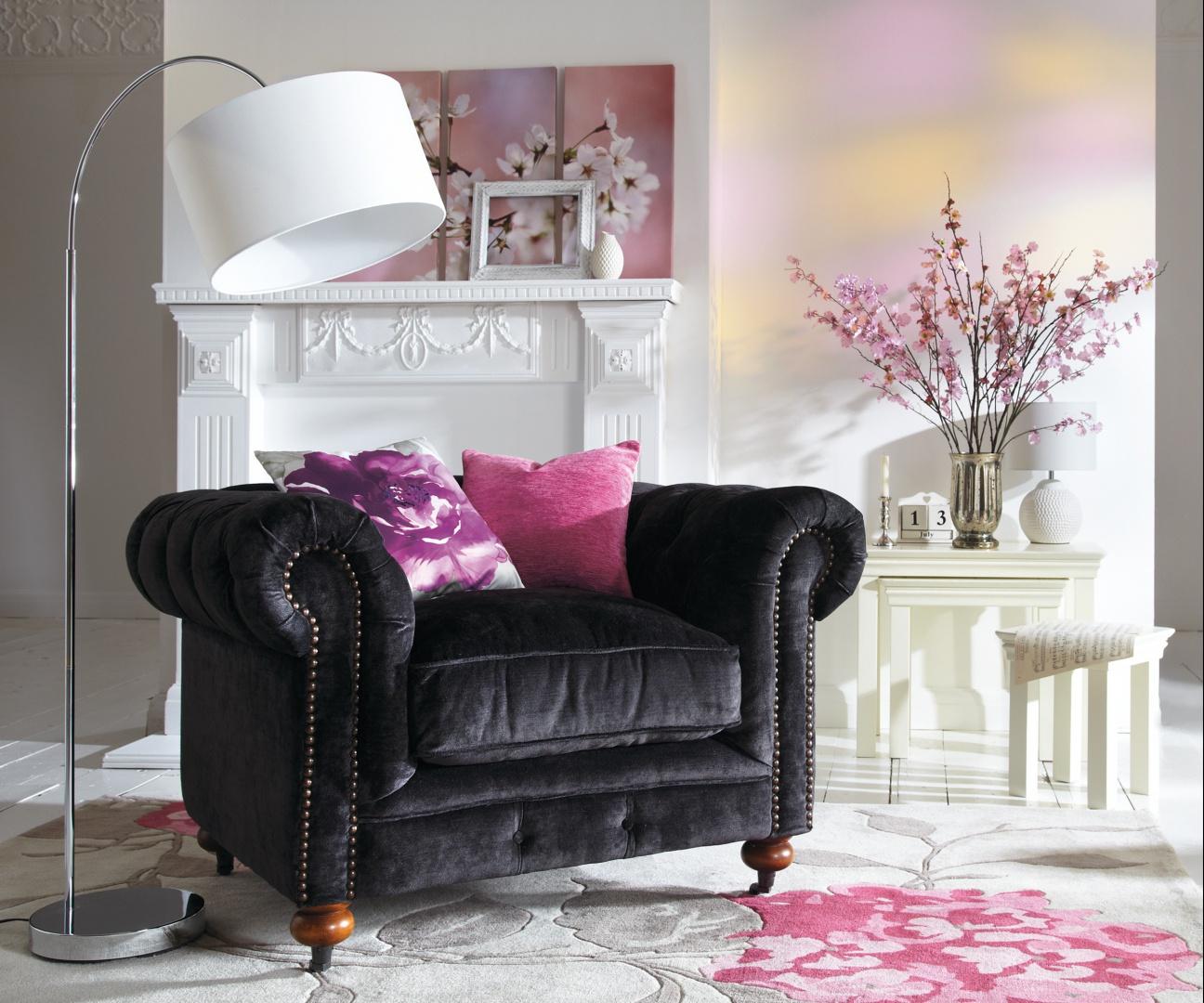 Z czarnymi meblami doskonale harmonizują różowe dodatki, np. poduszki dekoracyjne. Fot. Isme.