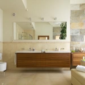 W utrzymanej w ciepłych beżach łazience naturalne materiały - kamień i drewno stanowią ciekawy element dekoracyjny. W podwieszaną szafkę wmontowano dwie duże umywalki. Projekt