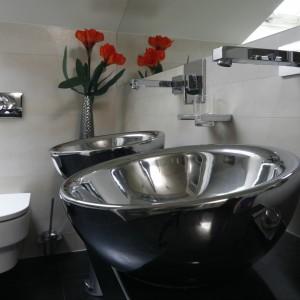 Zaprojektowana dla dwojga strefa umywalkowa urządzona została w nowoczesnym stylu, który przełamują dwie umywalki nablatowe w srebrnym kolorze. Projekt Piotr Stanisz. Fot. Bartosz Jarosz.