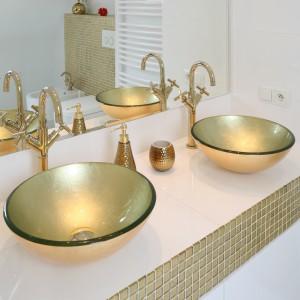 W skąpanej w złocie łazience nie mogło zabraknąć pięknych, pozłacanych mis umywalkowych. Ich niewielkie gabaryty podkreślają subtelny urok aranżacji. Projekt Piotr Stanisz. Fot. Bartosz Jarosz.
