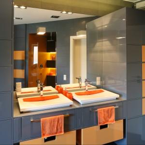 W szaro-pomarańczowej łazience strefa umywalkowa została zintegrowana ze strefą przechowywania. W jej centrum umiejscowiono dwie nablatowe umywalki o prostej zgeometryzowanej formie. Projekt Monika i Adam Bronikowscy. Fot. Bartosz Jarosz.