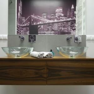 W nawiązującej swą stylistyką do wielkomiejskich przestrzeni łazienka utrzymana została w neutralnych kolorach. Podkreślają to szklane, transparentne misy umywalek zamontowane na drewnianym blacie szafki umywalkowej. Projekt Agnieszka Żyła. Fot. Bartosz Jarosz.