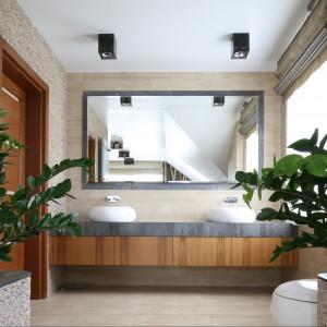 W przestronnej łazience urządzonej w konwencji SPA wydzielono odrębną strefę umywalkową. Spaja je wielkie lustro zamontowane na prawie całą szerokość ściany. Projekt Karolina Łuczyńska. Fot. Bartosz Jarosz.