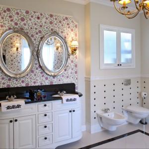 Utrzymana w angielskim stylu łazienka została pomyślana jako uroczy salonik kąpielowy Pani i Pana domu. Podkreślają to dwie umywalki podblatowe wmontowane w czarny blat stylizowanej szafeczki oraz dwa lusterka zamontowane tuz nad nimi. Projekt Maciej Bołtruczyk. Fot. Monika Filipiuk-Obałek.