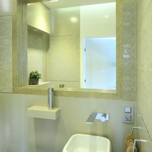 Utrzymana w jasnokremowej tonacji łazienka przyciąga wielością zdobnych elementów. Złota mozaika oraz płytki z neobarokowym motywem doskonale prezentują się na tle jednolitych, błyszczących płytek bazowych. Projekt Agnieszka Hajdas-Obajtek. Fot. Bartosz Jarosz.
