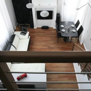 Salon z antresolą jest sercem tego dwupoziomowego apartamentu. Jego nieprzeciętna wysokość - 5,5 m buduje klimat otwartej, niczym nieograniczonej przestrzeni. Przestronne okna, od sufitu do podłogi, wpuszczają dużo światła. Projekt Michał Mikołajczak. Fot. Bartosz Jarosz.