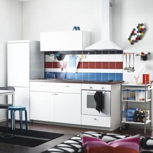 Zestaw mebli kuchennych z programu Metod/Häggeby. Białe drzwi i fronty szuflad Häggeby oraz szuflady Förvara. Obudowy szafek oraz fronty wykończone są folią melaninową. Szuflada Förvara ze stali malowanej proszkowo. Laminowany blat Säljan imitujący orzech. Uchwyty Attest z niklowanego aluminium. Cena: 2.990 zł, IKEA.