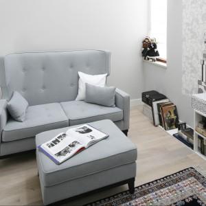 Salonik wypoczynkowy został urządzony w monochromatycznych barwach. Jasnoszara kanapa z dużym podnóżkiem stanowi perfekcyjnie dobrany element dekoracyjny, który dodaje przestrzeni osobowości. Projekt Magdalena Smyk. Fot. Bartosz Jarosz.