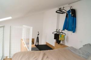 Nowoczesna sypialnia usytuowana na antresoli w... kawalerce, zaprojektowana przez pracownię Mili Młodzi Ludzie.