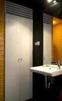 Paleta kolorystyczna zastosowana w łazience stoi pod znakiem żółtych i czarnych płytek ceramicznych oraz białej armatury.