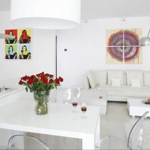 Kolorowe akcenty w achromatycznej przestrzeni stanowią popartowski plakat z wizerunkiem kobiety oraz – także dzielony na cztery części – obraz na płótnie. Projekt: Piotr Gierałtowski. Fot. Bartosz Jarosz.