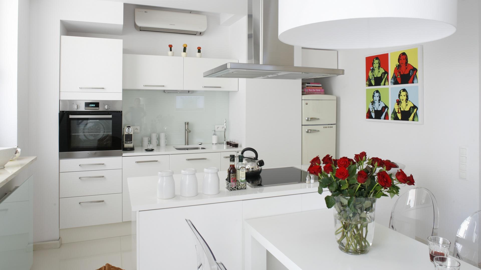 Otwarta kuchnia jest wyraźnie wydzielona w przestrzeni dziennej: za pomocą obniżonego fragmentu sufitu, materiału podłogowego (wielkoformatowe płytki gresowe) oraz wyspy ze znajdującym się nad nią okapem. Projekt: Piotr Gierałtowski. Fot. Bartosz Jarosz.
