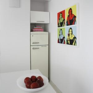 Przestrzeń nad lodówką wykorzystano na dodatkową szafką. W małej kuchni na pewno się przyda. Projekt: Piotr Gierałtowski. Fot. Bartosz Jarosz.