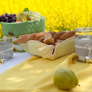 Żółty obrus, koszyczek na chleb oraz inne akcesoria tekstylne marki Dekoria przydatne nie tylko w ogrodzie. Fot. Dekoria.
