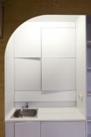 Funkcjonalna, monochromatyczna (utrzymana w bieli) kuchnia, której charakterystycznym rysem jest wykorzystanie każdego skrawka przestrzeni.