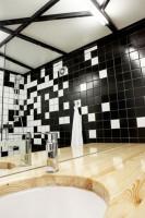 Dominantę kolorystyczną aranżacji prezentowanej łazienki stanowi nieregularny układ białych i czarnych płytek, którymi wykończono ściany.