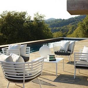 Białe fotele z kolekcji marki Gloster wyróżnia ciekawa forma siedzisk oraz charakterystyczny wzór w poziome pasy. Fot. Gloster.