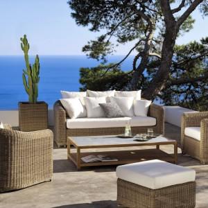 Zestaw wypoczynkowych mebli rattanowych w ciepłym, naturalnym kolorze z kolekcji Orlando marki Manutti w komplecie z eleganckimi białymi poduszkami na siedziska. Fot. Manutti.