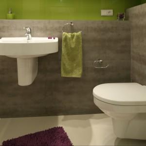 Stonowane, szare płytki  gresowe doskonale ożywia szkło na ścianach – hartowane i malowane od spodu na soczysty zielony kolor – sprawiając, że wnętrze jest lekkie i rześkie. Duet idealny! Projekt Marta Kruk. Fot. Bartosz Jarosz.