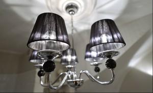 W tej łazience biel i drewno  tworzą układ odwołujący się do ponadczasowych wzorów. Kafelki na podłodze i ścianach wraz z ciężkimi, drewnianymi meblami przywodzą na myśl wnętrza zabytkowych kamienic. Z kolei żyrandol oraz lampki przy lustrze wnoszą nutę stylu glamour.