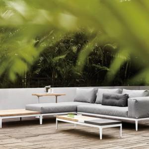 Czyste linie brył oraz elastyczne elementy modułowe kolekcji Grid marki Gloster uzupełniają miękkie poduchy w jasnoszarym kolorze. Całość wprowadza do ogrodu przytulną atmosferę salonu. Fot. Gloster.