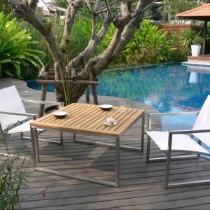 Duży, kwadratowy stół z kolekcji Ananta marki Deesawat charakteryzuje się w pełni zgeometryzowaną formą. Jego podstawę wykonano z aluminium, a blat z drewna teakowego. Fot. Deesawat.