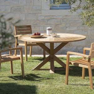 Wykonany z drewna teakowego stół marki Ethimo wyróżnia okrągły blat oraz ciekawa konstrukcja podstawy. Uwagę przyciąga ciepłe wybarwienie drewna. Fot. Ethimo.