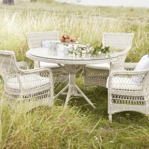 Białe meble rattanowe marki Sika Design o klasycznym kształcie oraz splocie. W komplecie okrągły stół z blatem zabezpieczonym szkłem. Fot. Sika Design.