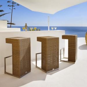 Stołki barowe z kolekcji Aspen marki Manutti wykonane zostały z rattanu o ciepłym, miodowym wybarwieniu. Uwagę przyciąga także ich zgeometryzowana forma. Fot. Manutti.