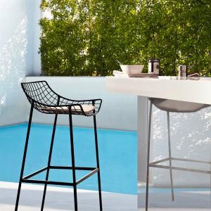 Wykonane z aluminium krzesło barowe marki Varaschin z ażurowym siedziskiem dostępne jest w kolorze eleganckiej czerni. Fot. Varaschin.