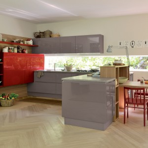 Meble do kuchni z kolekcji Extra.go firmy Veneta Cucine. Mimo zastosowania koloru czerwonego wnętrze pozostało bardzo spokojne, stonowane. Czerwone dodatki nadały mu jednak bardziej indywidualny wyraz. Fronty lakierowane na wysoki połysk.