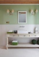Ta łazienka samym swoim wyglądem przenosi w klimat relaksu i odpoczynku. Biel pięknie zgrywa się z delikatną zielenią i drewnianym sufitem, tworząc połączenie przywodzące na myśl naturę. Elegancki akcent z kolei stanowią meble z rzeźbionymi elementami i wolnostojąca wanna na lwich nogach.