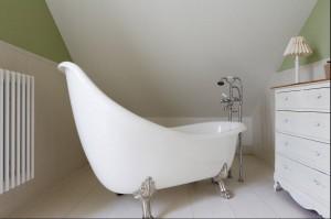 Ta łazienka samym swoim wyglądem przenosi w klimat relaksu i odpoczynku. Biel pięknie zgrywa się z delikatną zielenią i drewnianym sufitem, tworząc połączenie przywodzące na myśl naturę. Elegancki akcent z kolei stanowią meble na rzeźbionych nogach i wolnostojąca wanna na lwich nogach.