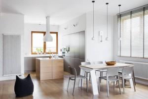 Masywny drewniany stół wygląda na lżejszy, dzięki białemu wykończeniu i lekkich krzesłach z tworzywa (Juno od Arper). Żaluzje na oknie nastrojowo oświetlają tę przestrzeń naturalnym, dziennym światłem.