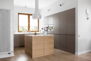 Kuchnia opiera się na prostych bryłach zlicowanych ze ścianą. Po środku kuchni stanęła prosta, monolityczna wyspa, na której skupia się całe gotowanie.