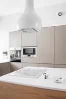 Biała kropla zawieszona nad wyspą to okap Drop od Faber. Jego rzeźbiarska forma ożywia proste wnętrze kuchni.
